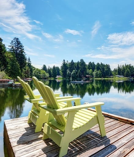 Green chairs on deck over lake