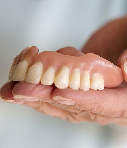 hand holding top dentures