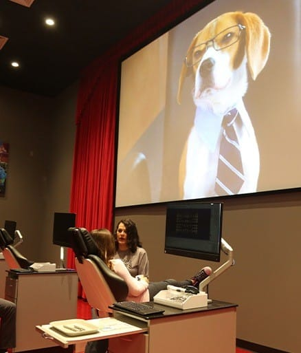 Glenpool team member working with dog with glasses on giant screen