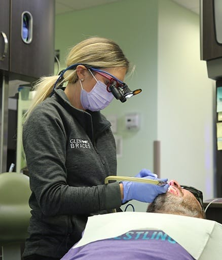 Glenpool team member performing dental cleaning